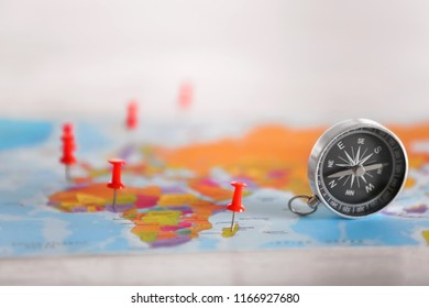 Modern compass with pushpins on world map