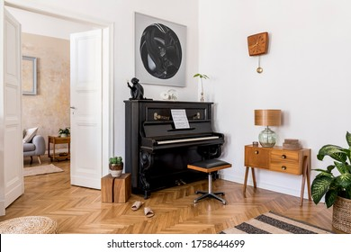 Modern composition of home interior with stylish black piano, design furnitures, plants, decoration, flowers, mock up painitngs and elegant personal accessories in trendy home decor.