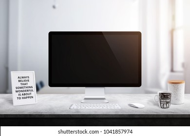 Modern computer display on office desk. Picture frame, box and coffee mug beside.
