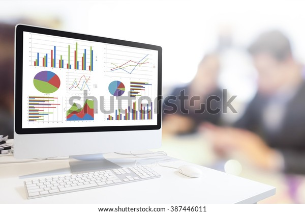 Modern computer with keyboard and mouse on table showing charts and graph against blurred business people background , Analysis Business, Statistics Concept.