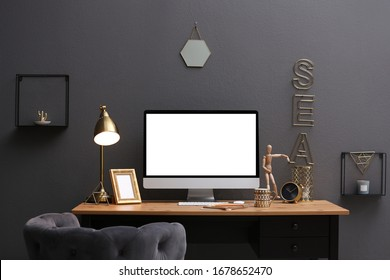Modern computer on table in stylish office interior