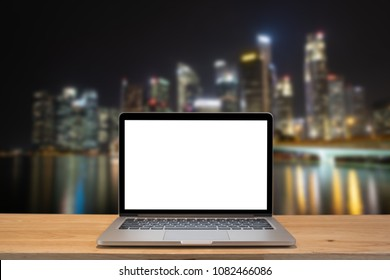 Modern computer,laptop with blank screen on wood table with office window view on blurry singapore night city background