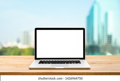 Modern computer,laptop with blank screen on wood table with office window and city view backgrounds