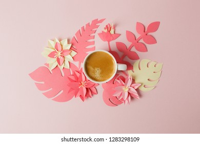 Modern concept of romantic morning breakfast - cup of coffee espresso and origami papercraft flowers and plants on pink pastel table