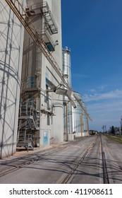 A modern concrete grain elevator complex with railroad tracks
