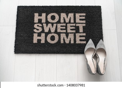 Modern condo businesswoman high heel shoes at home on entrance doormat saying Home Sweet Home welcoming homeowner after a day at work at new house background concept. Fashion grey suede kitten heels.