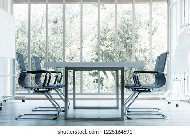 Modern conference room with furniture and large windows, outside nuture view, soft focus.