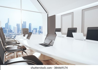 Modern conference room with oval table, chairs, laptops, big window and city view,