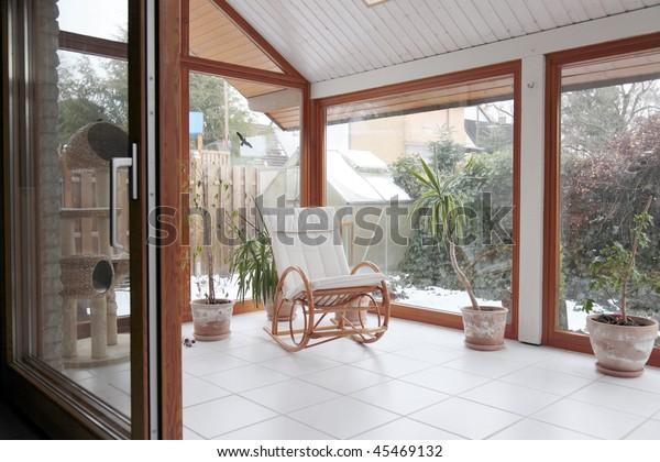 modernes Wintergarten mit Schaukelstuhl