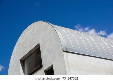 Modern construction. Metal ribbed arch-span roof covering. Looking up .