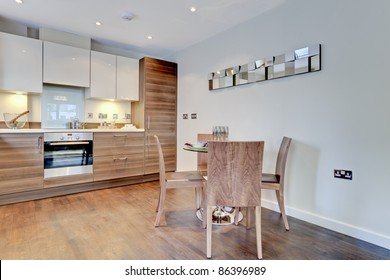 Modern contemporary breakfast kitchen with built in appliances, table and chairs