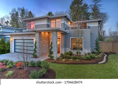 Modern contemporary house exterior with luxury details, landscaping, stone, wood, glass, lots of large windows with evening lights and red front door.