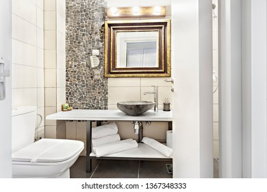 Modern contemporary interior bathroom with sink and mirror, glass walk in shower with marble tile surround