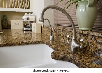 Modern contemporary kitchen interior with granite worktop and cream units, focus on the sink area.