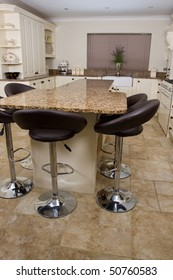 Modern contemporary kitchen interior with granite worktop and cream units and black stools
