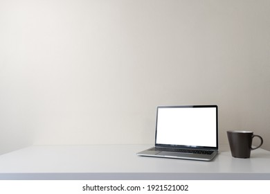 Modern contemporary workspace with blank screen laptop computer and coffee cup on office desk table on white wall background for copy space. Home office workplace concept.