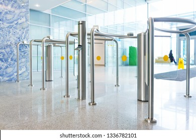 Modern control and security systems. Access system in an office building. Stylish turnstiles made of glass and metal in the lobby of an unrecognizable business center. Soft focus and beautiful bokeh.