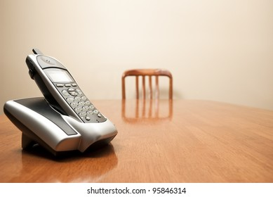 A modern cordless phone sits on an empty table