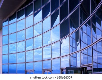 A modern corporate building with a curved facade reflecting the sky