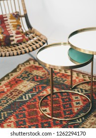 Modern cosy metal and natural rustic wicker rattan armchairs is supported by black sled style metal legs with pillow and colorful mosaic oriental kilim rug with traditional folk geometric