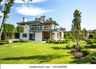 Modern country house with the large lawn and a wooden fence. In front of the house there is a covered terrace with a lounge zone. On the lawn there is a trees and flowerbeds. It is sunny.