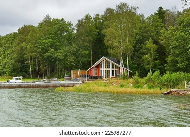 Modern country house on beach with pier and boat