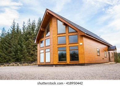 Modern countryside wooden house with facade with big glass windows. Fir trees forest in the background.