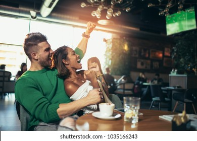 Modern couple in cafe looking excited and happy after their favorite football team scored a touchdown. Selective focus