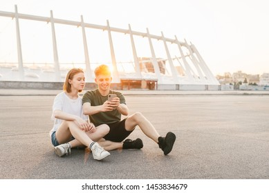 Modern couple of milenials sitting on the street in the background of a beautiful city landscape at sunset, using a smartphone and smiling. Students sitting on a beautiful urban background and relax.