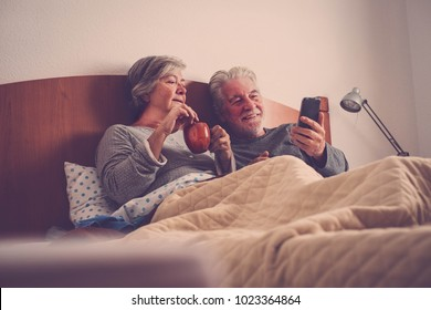 modern couple of seniors man and woman having breakfast at bed at home using mobile phone to read messages from parents and friends. Love together forever concept. Brown tones.