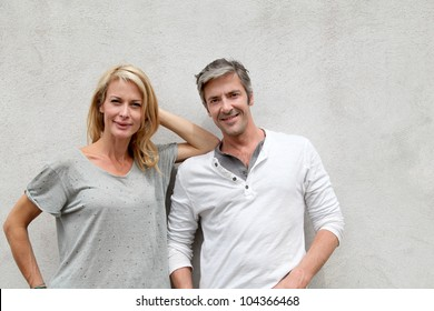 Modern couple standing on concrete wall