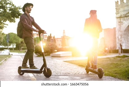 Modern couple using electric scooter in city park - Milenial students riding new ecological mean of transport - Green eco energy concept with zero emission -Bright warm filter with sunshine halo