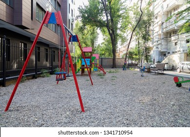 Modern courtyard in the new housing building. Colourful playground for children in public housing block.