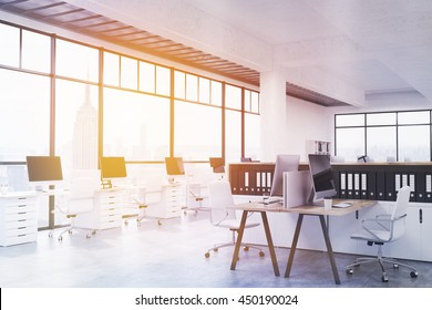 Modern coworking office interior with numerous workplaces, concrete floor, ceiling and panoramic windows with New York city view and sunlight. Toned image, 3D Rendering