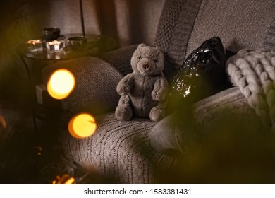 Modern cozy interior in gray shades with an armchair. On the chair there are nice knitted blanket, black sparkling cushion and Teddy bear. Blurred background and copy space.
