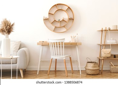 Modern and cozy interior of living room with a lot of rattan accessories, wooden desk, gray sofa, basket and wooden shelf. Korean style of home decor. Hanging rattan snail with airplants. Template.