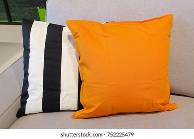Modern Cozy Sofa with Orange with Back and White Decorative Pillow, Close Up.