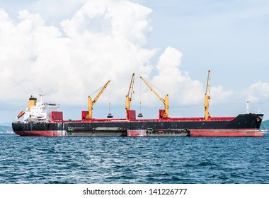 Modern crane in the large cargo ship is lifting the goods from small ship.