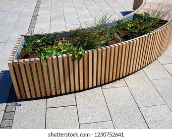 Modern creative trendy Scandinavian style urban outdoor wooden bench combined with flower planter city landscape