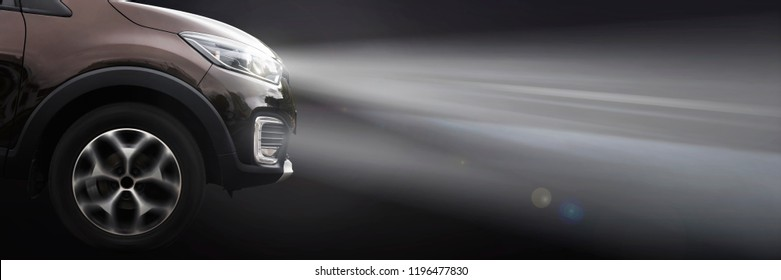 modern crossover car shines with headlights on a dark background. side view