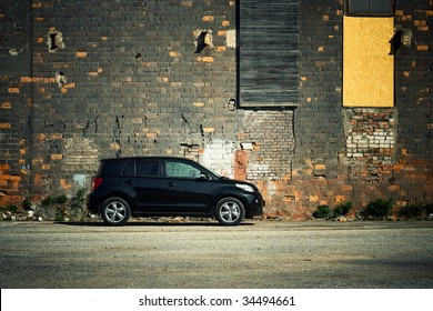Modern crossover vehicle near old brick wall
