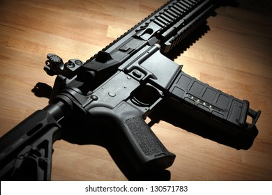 Modern custom AR-15 (M4A1) carbine on a wooden surface. Studio shot