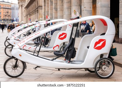 Modern cycle rickshaw. Velotaxi, bicitaxi bike taxi on parking lot waiting for tourists to ride through the downtown. Tricycle pedal taxi. Eco friendly transportation. Milan, Italy - October, 2019