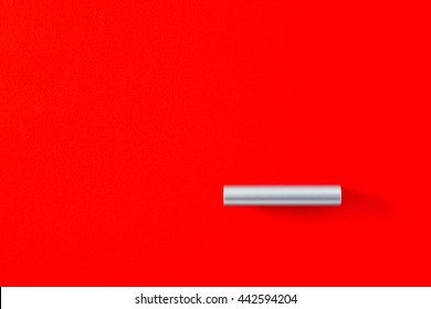 Modern cylindrical metal handle in the bottom right corner on a vivid wooden red cabinet in a full frame background view with copy space