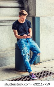 Modern daily life. Young American Man with little beard texting on cell phone in New York, wearing black T shirt, destroyed jeans, fashionable shoes, sitting on pillar in corner of vintage street.