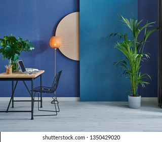 Modern dark blue stone wall, textured wall, blue decorative wall, chair vase of plant and table interior concept. Home wall background. laptop and technology interior room.