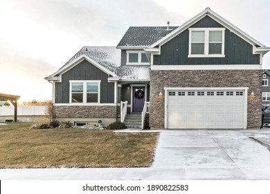 A modern dark gray and white new construction craftsman with stone accents and a purple front door in Salt Lake city on a snowy winter December day
