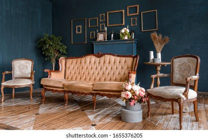 Modern dark interior with a fireplace, flowers, a cozy brown sofa with carved legs and two elegant armchairs. The stylization of the Baroque, classical design, historic interior.
