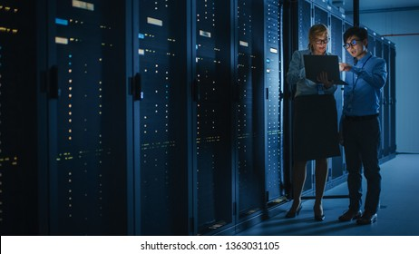 In the Modern Data Center: Engineer and IT Specialist Work with Server Racks, Talking, Doing System Maintenance Check with Laptop Computer. Concept of Diagnostics of the Database, Cybersecurity Check