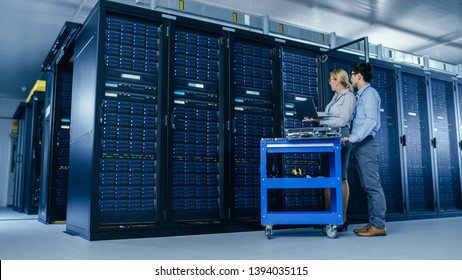 In the Modern Data Center: Engineer and IT Specialist Work with Server Racks, on a Pushcart Equipment for Installing New Hardware. Specialists Doing Maintenance of the Database. Low Angle Shot.